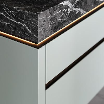 Salbeigrüne Küchenfront kombiniert mit Steinarbeitsplatte