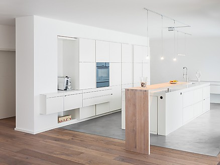 Moderne Küchenlösung von plan 3 küche aus weißem Corian mit Holzakzent