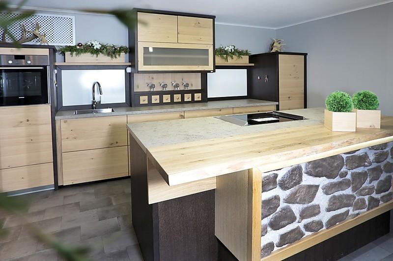Inselküche aus holz mit theke und sichtbaren astlöchern